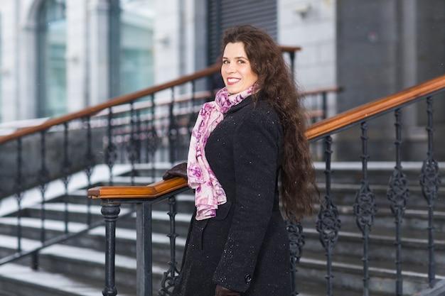 Mensen, mode en winter concept - jonge vrouw poseren in jas met op trap achtergrond