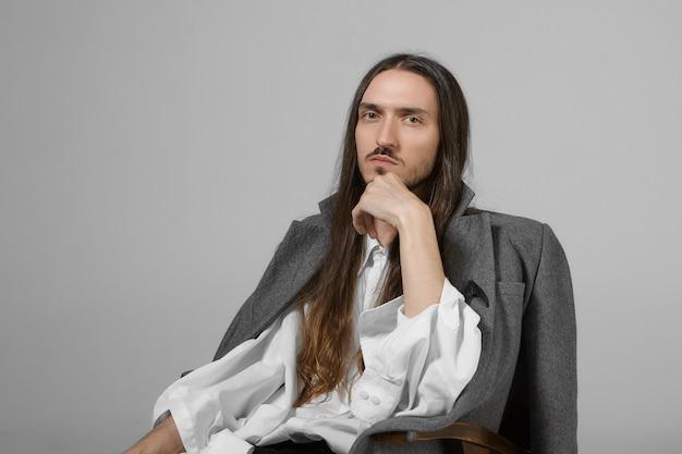 Mensen, mode, schoonheid en stijlconcept. foto van trendy uitziende modieuze jonge man met een wit overhemd en een stijlvolle grijze jas die hand op zijn kin houdt, met een serieuze doordachte blik