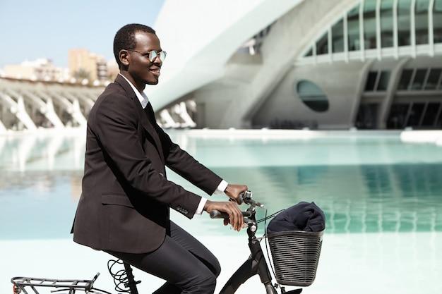 Mensen, moderne levensstijl, transport en ecologie concept. succesvol, ecologisch vriendelijk, donkerhuidig mannelijk hoofd van een groot financieel bedrijf dat op de fiets naar kantoor gaat en een zwart formeel pak draagt