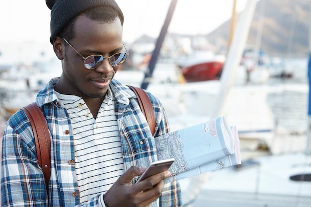 Mensen, moderne technologie, communicatie, reizen en toerisme concept. knappe jonge afro-amerikaanse backpacker met papieren kaart en mobiele telefoon, messaging online terwijl net aangekomen in de nieuwe stad