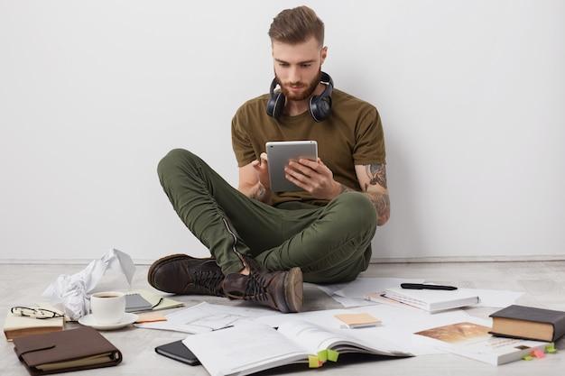 Mensen, moderne technologie en onderwijsconcept. stijlvolle man met baard draagt laarzen, zit gekruiste benen op de vloer,