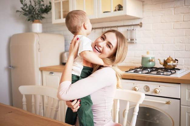 Mensen, moederschap, liefde, familie en relaties concept. portret van gelukkige mooie jonge vrouw zitten in een stijlvolle keuken interieur knuffelen haar schattige zoontje, op zoek met vrolijke glimlach