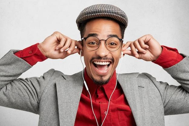 Mensen, muziek, plezier en vreugde concept. aantrekkelijke man met gelukkige uitdrukking, draagt trendy pet,