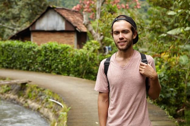 Mensen, natuur en zomer concept. stijlvolle jonge ongeschoren hipster man met snapback en rugzak ontspannen buiten tijdens het wandelen langs de landweg in landelijk gebied
