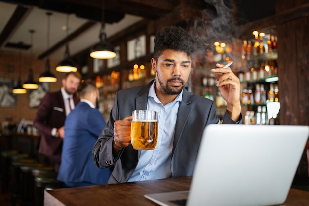 Mensen, nicotine alcoholverslaving en slechte gewoonten concept. close up van man bier drinken, sigaret roken bij bar