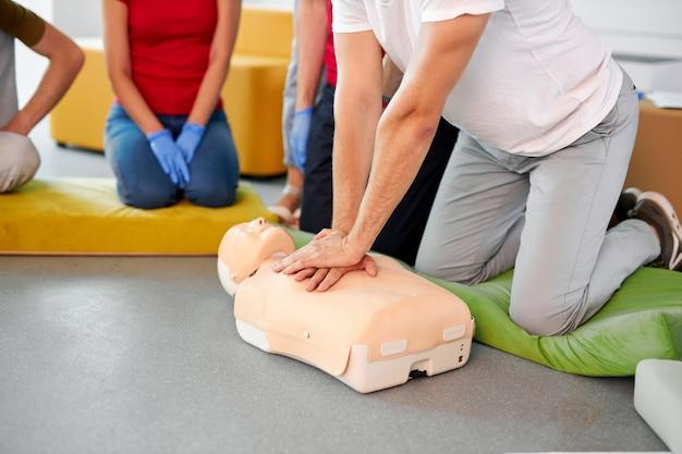 Mensen oefenen een reanimatieoefening tijdens de reanimatie-les