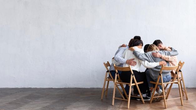 Mensen omhelsden elkaar in een kring tijdens een groepstherapiesessie