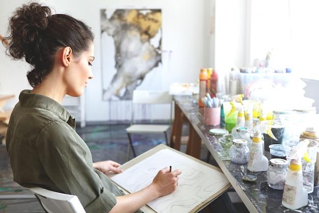 Mensen, onderwijs en creativiteit concept. profiel van een jonge vrouw met krullend haar in paardenstaart leren hoe te schetsen en tekenen terwijl u deelneemt aan kunst workshop of klasse