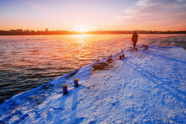 Mensen op de pijler die op de zonsondergang letten. silhouet van vissers