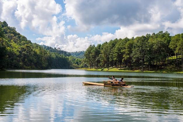 Mensen op een boot op een meer met bomen