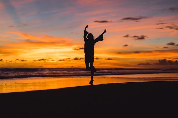 Mensen op het strand bij zonsondergang. het meisje springt tegen de achtergrond van de ondergaande zon.
