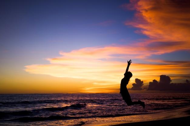 Mensen op het strand bij zonsondergang. het meisje springt