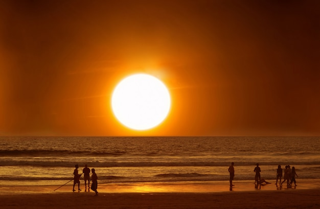 Mensen op het strand in het water bij zonsondergang, oceaan, vakantie.