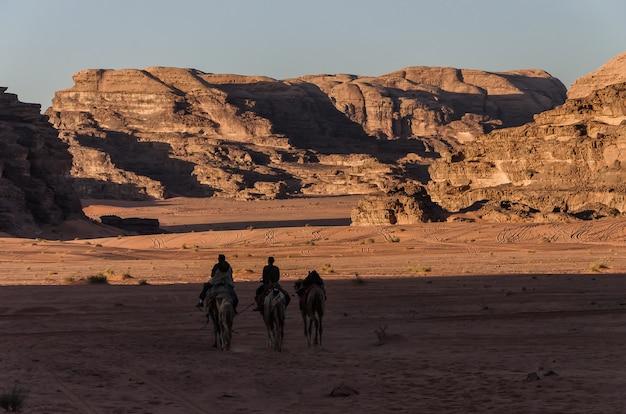 Mensen op kamelen die door de woestijnstorm gaan