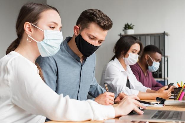 Mensen op kantoor die werken tijdens een pandemie met maskers aan