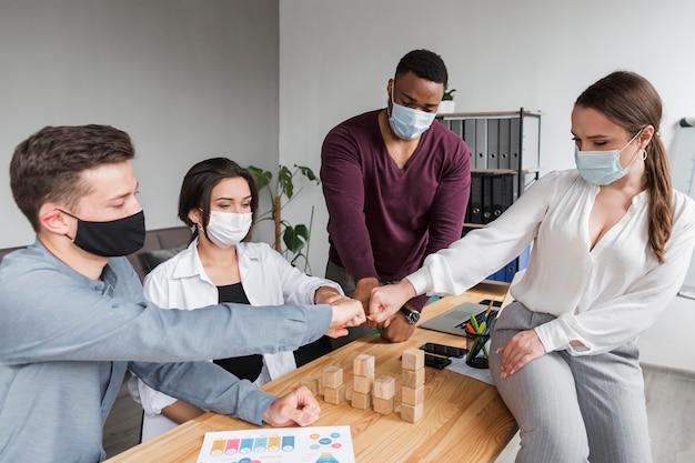 Mensen op kantoor tijdens een pandemie die een vergadering hebben en elkaar stoten