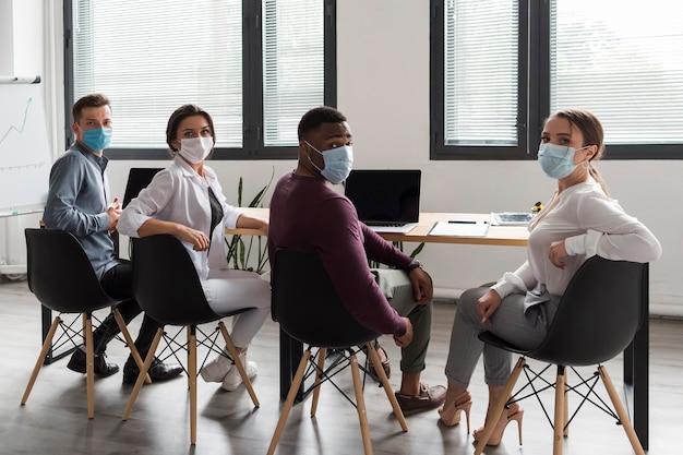 Mensen op kantoor tijdens pandemie werken terwijl ze medische maskers dragen