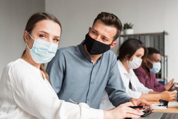 Mensen op kantoor werken samen tijdens een pandemie met maskers op