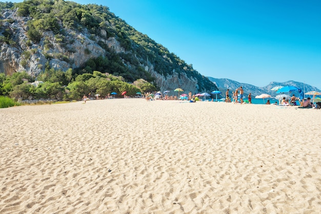 Mensen op tropisch strand met geel zand. zomervakantie aan de blauwe zee