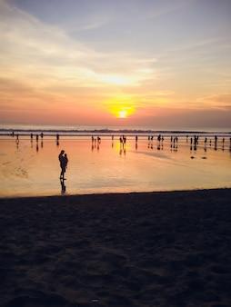 Mensen op zonsondergang achtergrond op zandstrand
