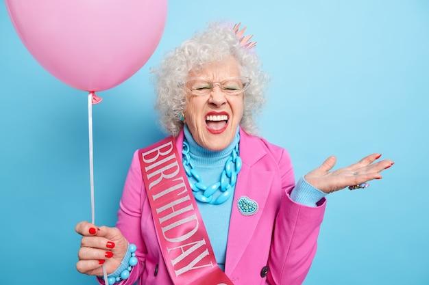 Mensen oude mensen vakantie concept. emotionele senior vrouw roept luid en drukt negatieve emoties uit houdt mond open, gekleed in feestelijke kleding houdt opgeblazen ballon vast