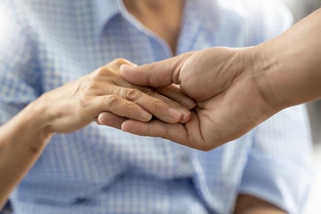 Mensen oude vrouw en jonge hand zorg bedrijf gezondheidszorg gehandicapten lopen met hulp