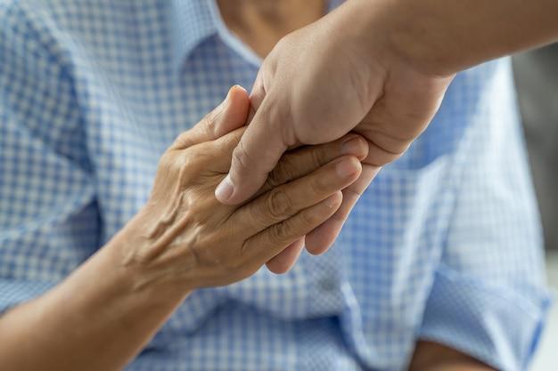 Mensen oude vrouw en jonge handholding gehandicapte het lopen met hulp