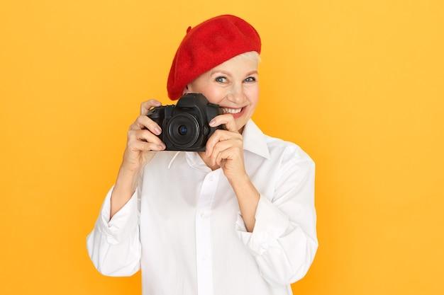 Mensen, ouder worden, pensioen en creatief beroepsconcept. portret van senior vrouwelijke fotograaf in witte blouse en rode motorkap full frame dslr camera te houden