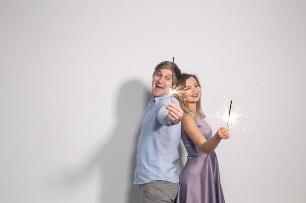 Mensen partij en vieringen concept jong koppel met wonderkaarsen rug aan rug op witte muur te blijven
