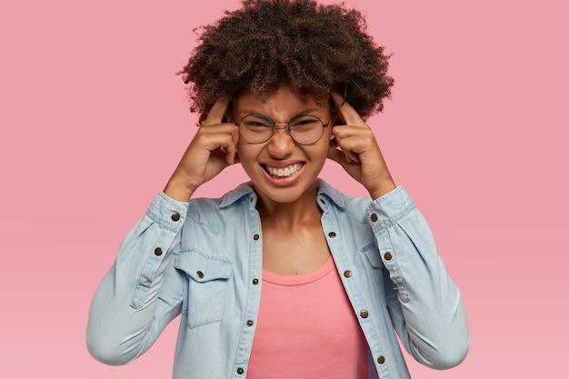 Mensen, pijn en negatieve gevoelens concept. donkere ontevreden dame fronst gezicht, houdt vingers op slapen, lijdt aan migraine, heeft vreselijke hoofdpijn, probeert zich te concentreren en informatie te onthouden