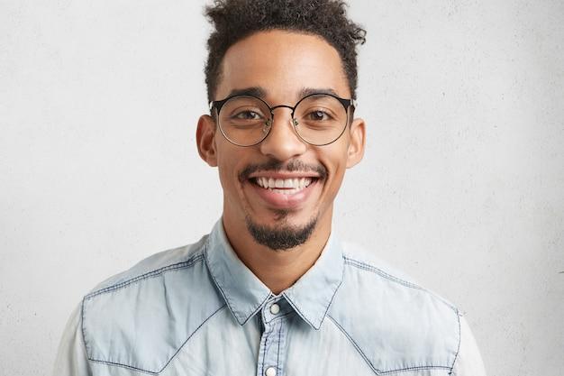 Mensen, positiviteit en geluk concept. blij dat lachende mannelijke tiener een grote bril draagt, gelukkig is