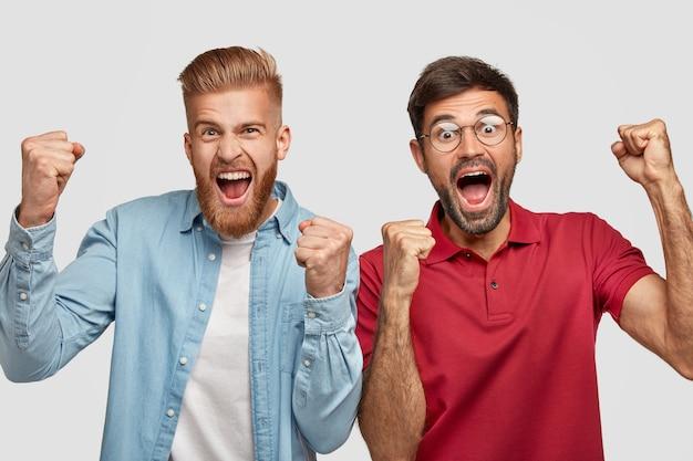 Mensen, prestatie en succesconcept. beste mannelijke vrienden balanceren hun vuisten van geluk, zijn opgewekt, openen de mond wijd, hebben dolgelukkige uitdrukkingen, vieren hun overwinning, poseren binnen