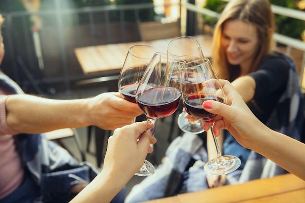 Mensen rammelende glazen met wijn op het zomerterras van café of restaurant
