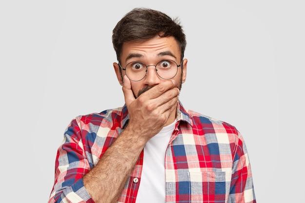 Mensen, reactie, emoties en gezichtsuitdrukkingen concept. bange europese man bedekt zijn mond, staart met angst