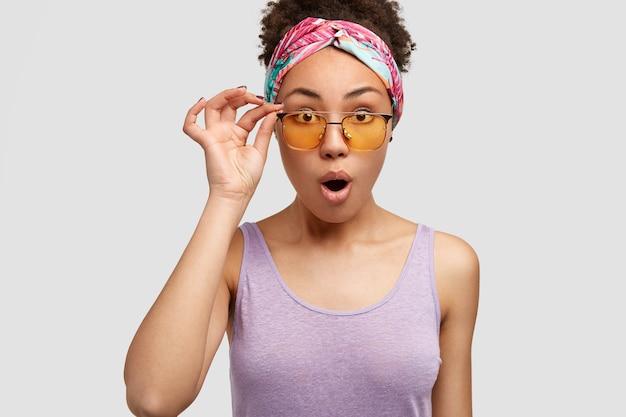 Mensen, reactie en gezichtsuitdrukkingen concept. mooie doodsbange vrouw met verbijsterde blik, draagt gele tinten en paars t-shirt, kijkt verrassend naar iets, poseert alleen op een witte muur