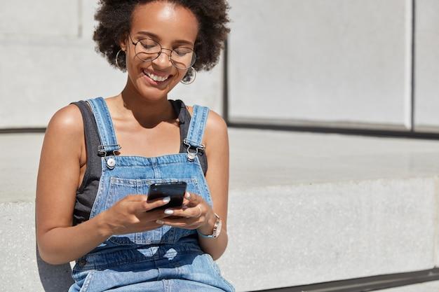 Mensen, recreatie en technologieconcept. ontspannen zorgeloze zwarte vrouw houdt mobiele telefoon in handen, typt sms naar vriend, heeft blije gezichtsuitdrukking, vrije ruimte gereserveerd voor uw tekstinformatie