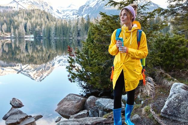 Mensen, recreatie, vrije tijd, levensstijlconcept. peinzende vrouw in gele regenjas, rubberen laarzen
