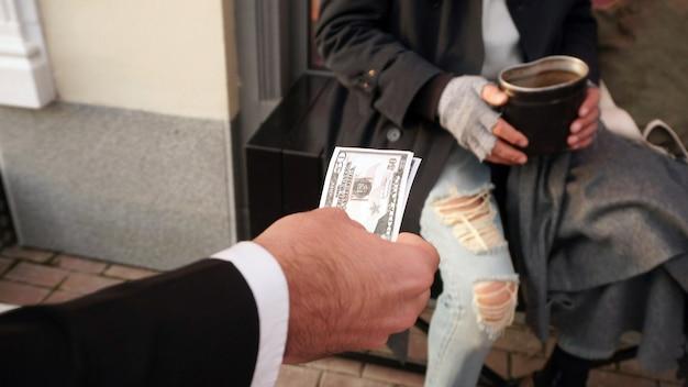 Mensen reiken geld uit, dollars naar een dakloze, een bedelaar om te helpen, om geld te geven voor een donatie