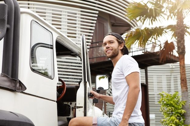 Mensen, reizen en avontuur concept. aantrekkelijke man met baard glimlachend en afscheid van zijn vrienden na een actief weekend in openlucht terwijl staande buiten zijn witte jeep