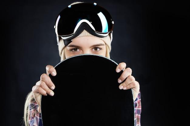 Mensen, reizen, recreatie en extreme sporten concept. portret van mysterieuze positieve jonge vrouw snowboarder met veiligheidsbril op haar hoofd, verstopt achter zwarte bord en op zoek
