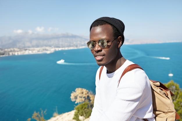 Mensen, reizen, toerisme en lifestyle. stijlvolle reiziger met donkere huidskleur die trendy kleding draagt die zich op berg boven zee bevindt