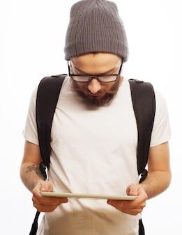 Mensen, reizen, toerisme en technologie concept - gelukkige jonge bebaarde man in bril met rugzak en tablet over witte ruimte. hipster-stijl. positieve emoties.