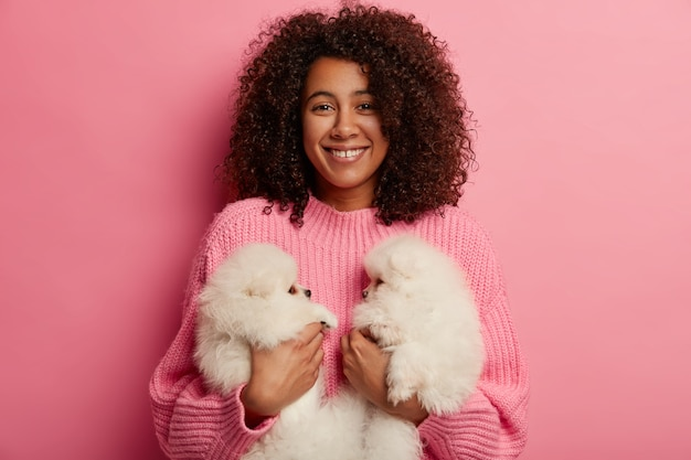 Mensen, relatie en genegenheid concept. positieve donkere gekrulde vrouw houdt twee puppy's vast