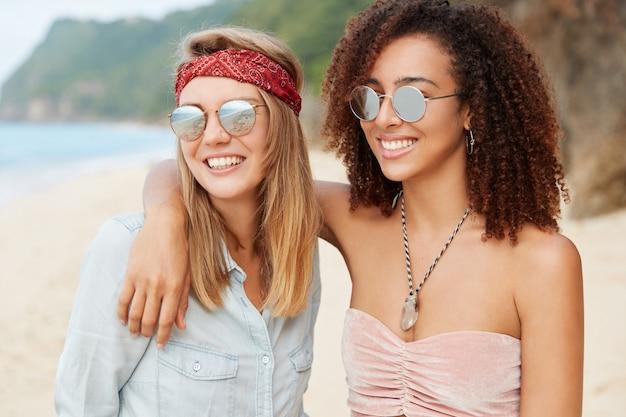 Mensen, relatie en rust concept. gepassioneerd gemengd ras lesbisch koppel poseert tegen prachtige zeeën met klif, hebben een brede glimlach, wandelen samen langs de kustlijn en knuffelen, kijken in de verte