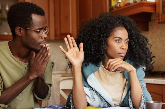 Mensen, relatieproblemen en echtscheiding. berouwvol bezorgd man met donkere huidskleur die de handen in elkaar gedrukt houdt, smekend beledigde vrouw om zijn ontrouw te vergeven, gekke vrouw die helemaal niet naar hem kijkt