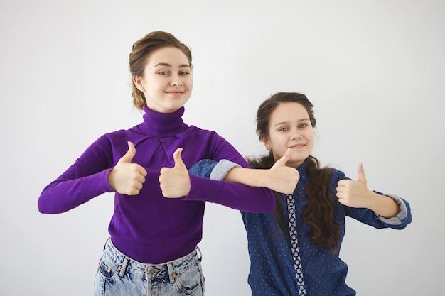 Mensen, relaties, familie en lichaamstaal. foto van emotionele jonge vrouw en haar tienerzus die naast elkaar staan