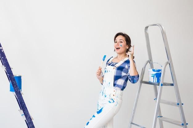 Mensen, renovatie en werkconcept - mooie vrouw die op de ladder staat en muren schildert.