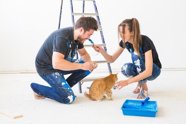 Mensen, renovatie, huisdier en reparatie concept - portret van grappige man en vrouw met kat die herinrichting in appartement doen.