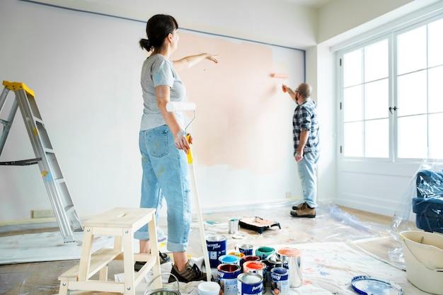 Mensen renoveren het huis door de muur te schilderen