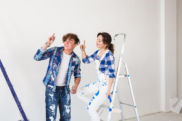Mensen, reparatie en relatie concept - jong grappig stel doet renovatie in nieuw appartement.